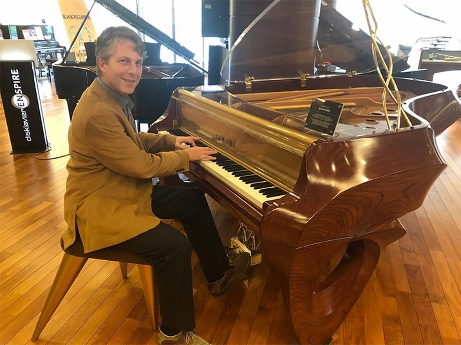 "Music entrepreneurship professor David Cutler, whose book ""The Savvy Musician"" focuses on how to turn a musical education into a successful career, poses with a piano."