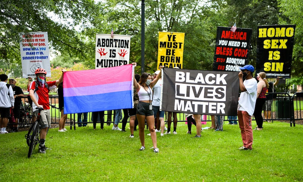 <p>University of South Carolina students hold a transgender pride flag and a Black Lives Matter flag in front of protestors on campus on Aug. 26, 2020.</p>
