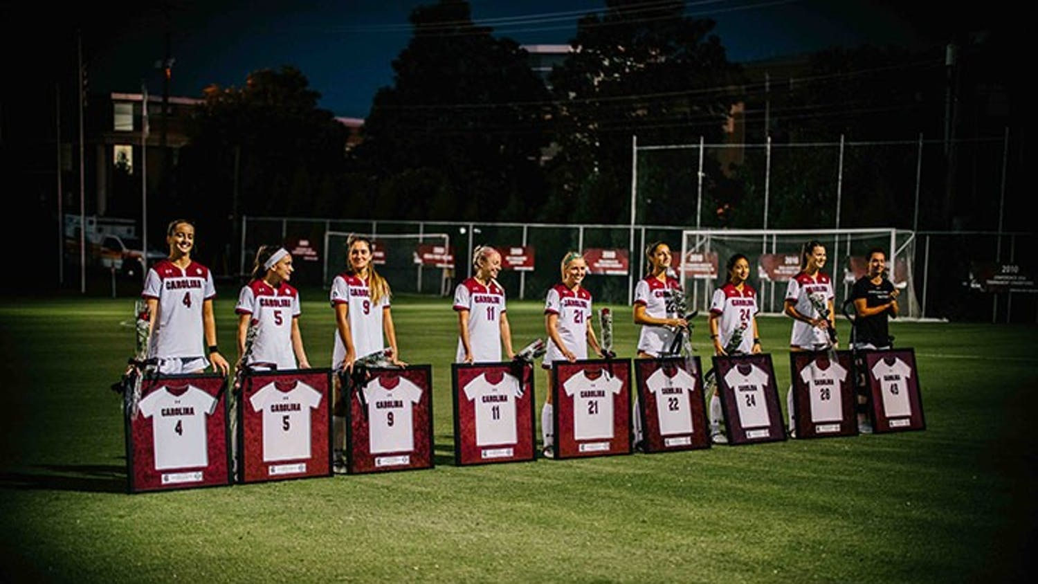 The seniors for the women's soccer team stand behind their framed jerseys. The team beat Mississippi State University 2-0 Friday, Oct. 30.