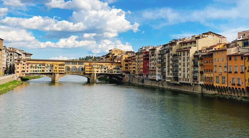 <p>A canal in Florence, Italy, that is faced by buildings on each side and has a bridge to let pedestrians cross the canal.&nbsp;</p>