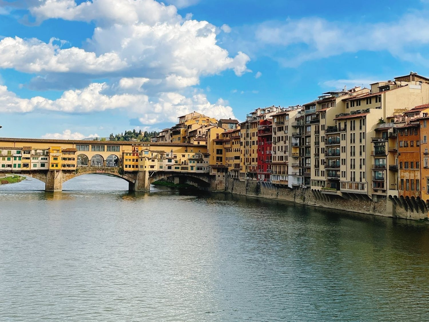 A canal in Florence, Italy, that is faced by buildings on each side and has a bridge to let pedestrians cross the canal.