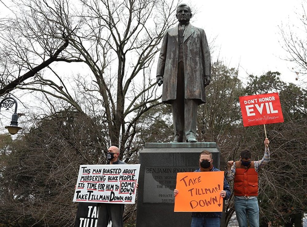 <p>Protesters stand in front of the Benjamin Tillman statue at the South Carolina Statehouse. The protesters are calling for the removal of the statue based on Benjamin Tillman's history.</p>