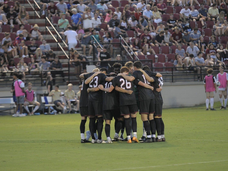 South Carolina men's soccer team huddle in a group.