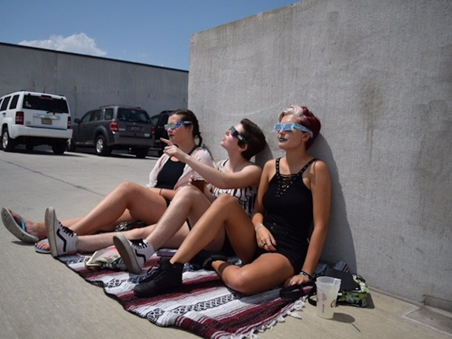 Students wear their protective glasses while watching the total solar eclipse on the top of a parking garage Aug. 21, 2017.