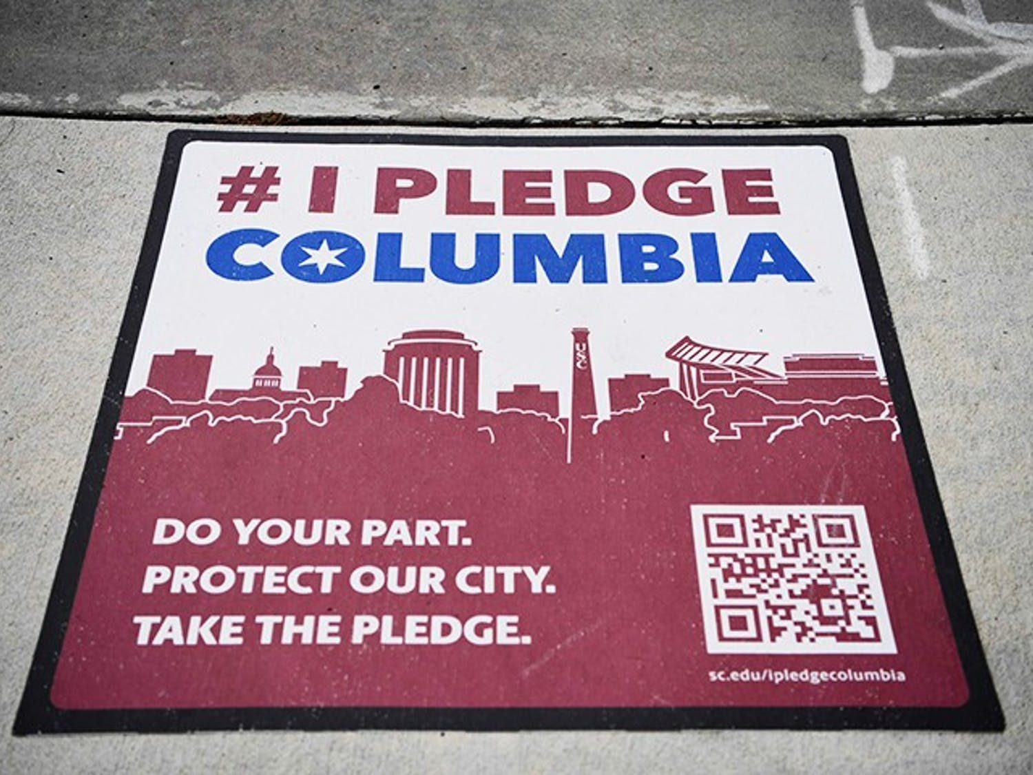 One of the many signs for #IPledgeColumbia sits on a sidewalk near campus.