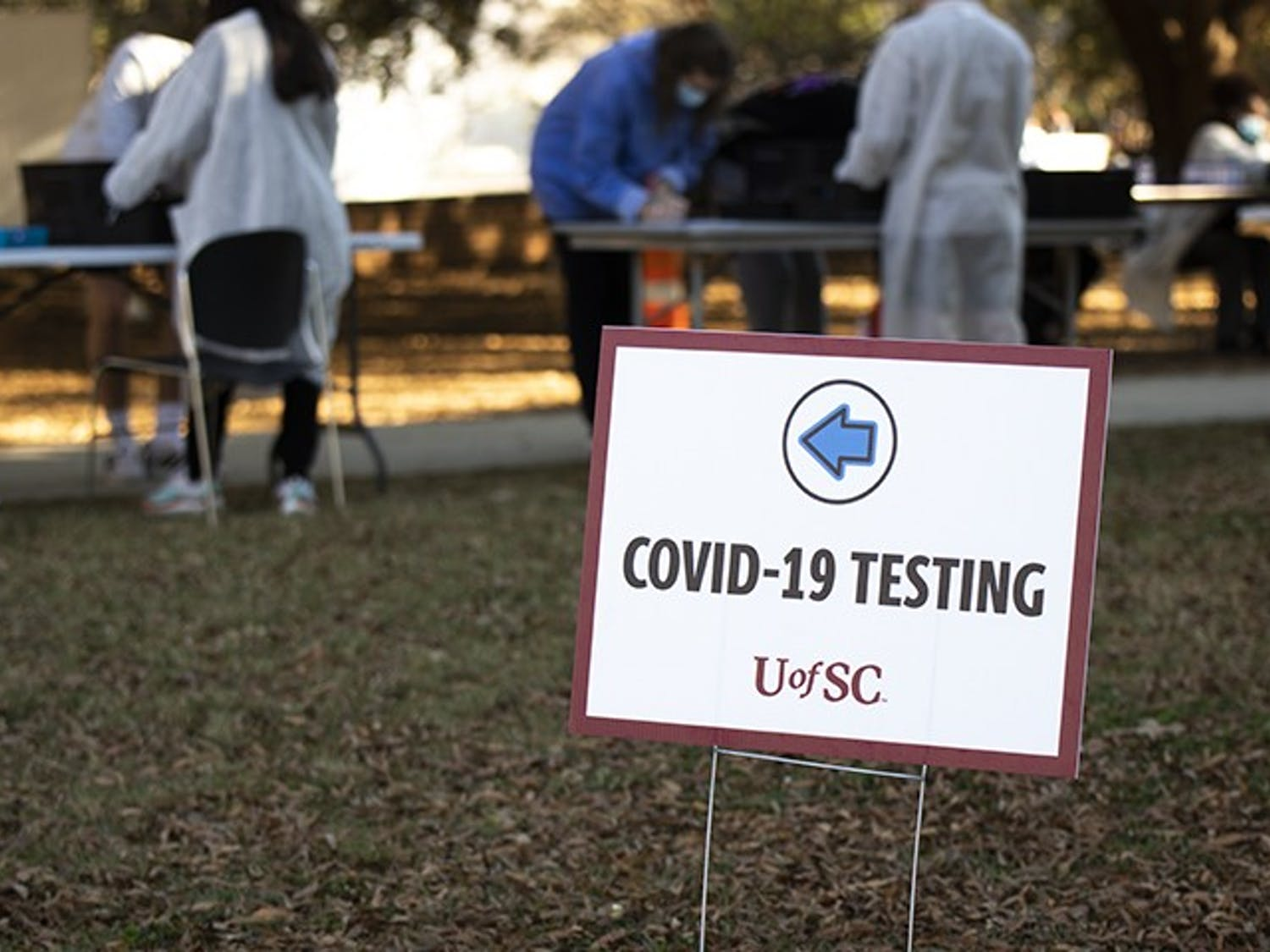 A sign marks the check-in area for COVID-19 testing on Davis Field. The university has had over 2,800 students test positive for the virus since Aug. 1.