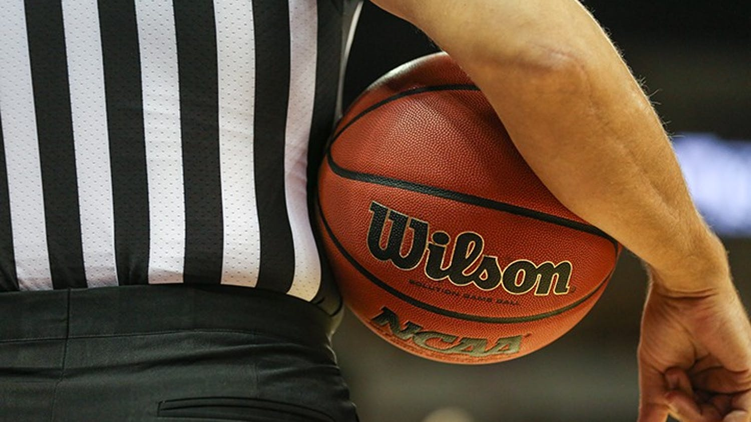 A referee holds a basketball under his arm during a timeout in a 2019 game at Colonial Life Arena.