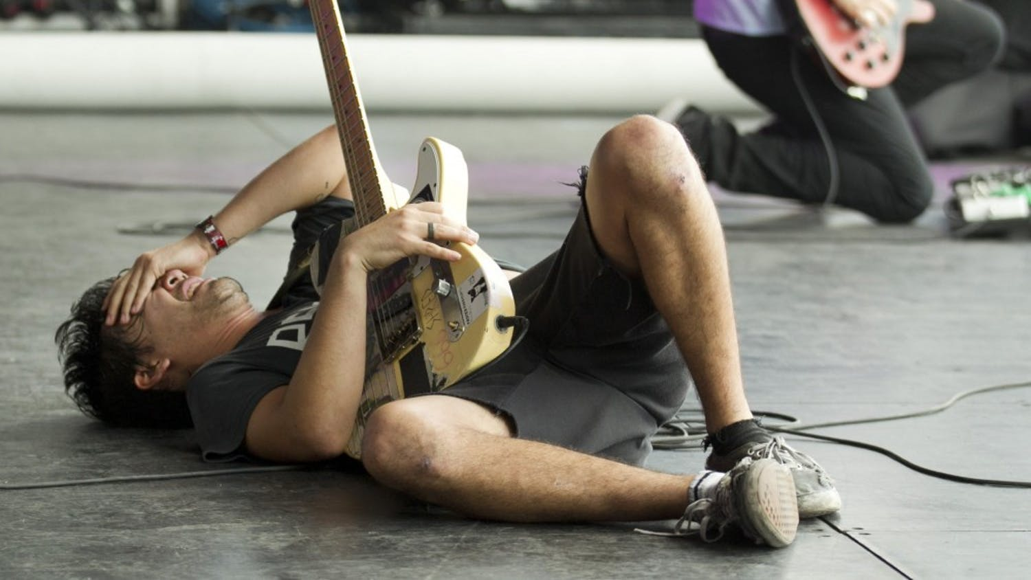 Zac Carper, of the Los Angeles skate punk band FIDLAR, falls to the stage near the end of his set at the Austin City Limits Music Festival in Austin, Texas in October 2013. (Jay Janner//Austin American-Statesman)