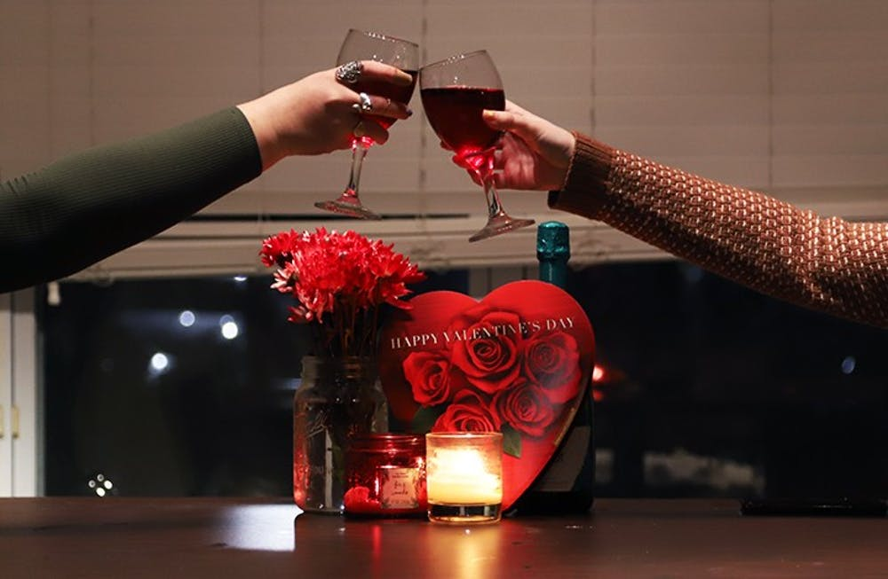 <p>Two girls clink their glasses together with Valentine's Day paraphernalia behind them.</p>