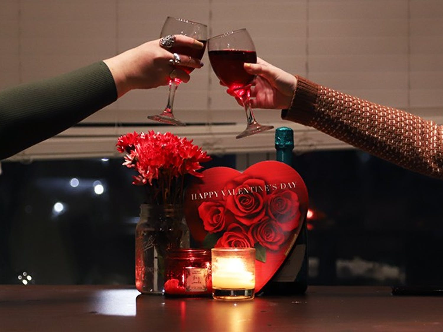 Two girls clink their glasses together with Valentine's Day paraphernalia behind them.