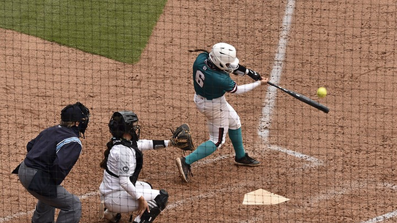 """Junior catcher Jordan Fabian connects on a pitch in Sunday's game against the University of Central Florida. The Gamecocks wore teal for """"All for Alex,"""" which is an organization that aids in the fight against ovarian cancer."""
