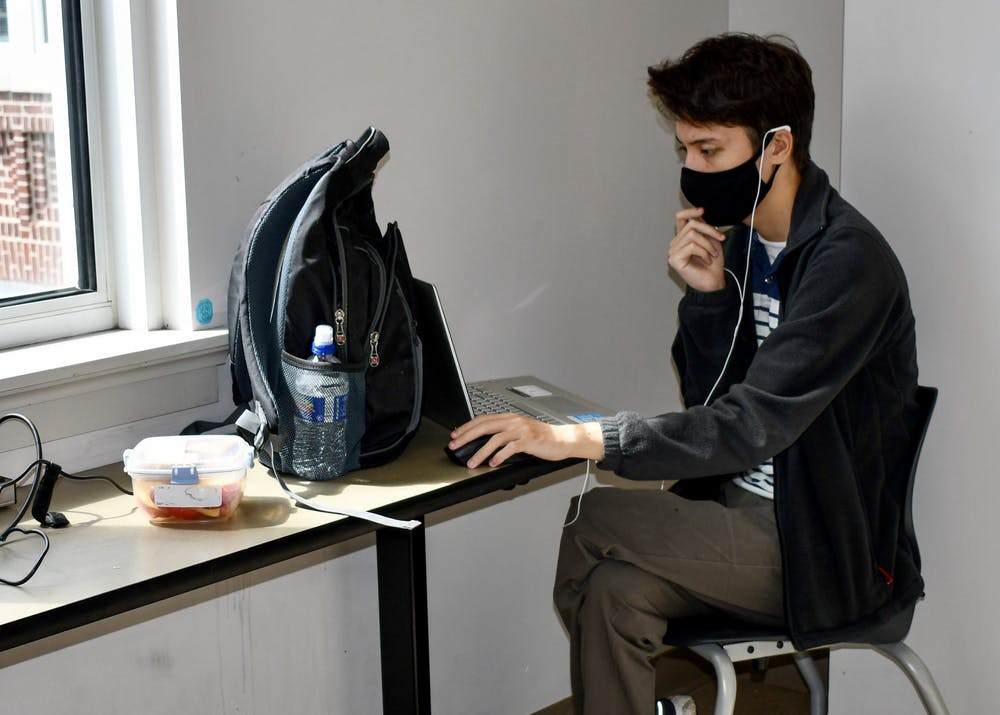 <p>A student works virtually on his computer. All students are required to wear a mask while on campus.</p>
