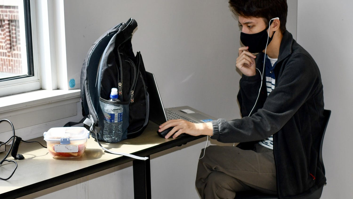 A student works virtually on his computer. All students are required to wear a mask while on campus.
