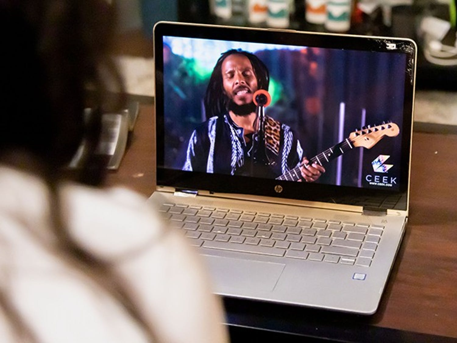 A person sits on their couch while streaming a concert on their laptop. Live-stream concerts became popular during the COVID-19 pandemic as they provided a safe way to attend and enjoy music entertainment.