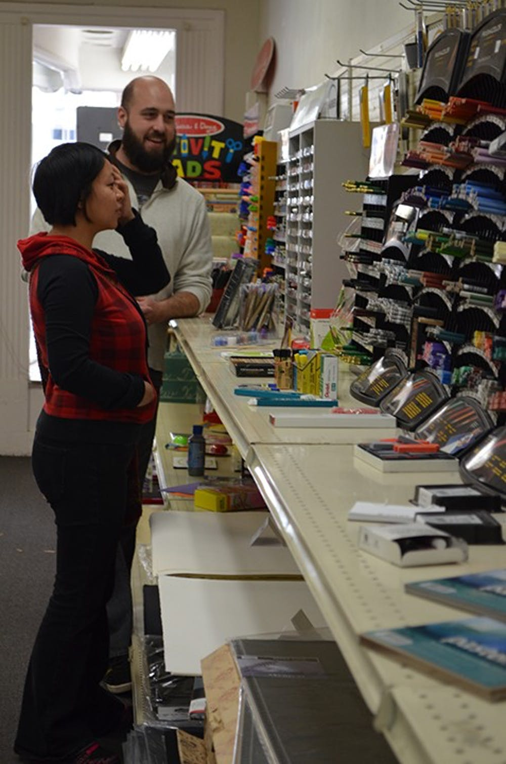 <p>S&amp;S Art Supply owner Eric Stockard helps a customer choose supplies. The store will close this month.</p>
