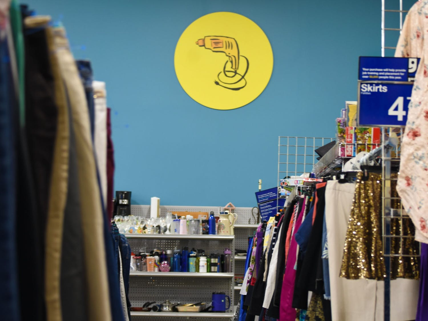 An aisle within a Goodwill retail store. The act of thrifting and the rise of secondhand-centered e-commerce apps have become popular among college students who seek to buy clothing at lower prices and combat unsustainable practices within the fashion industry.