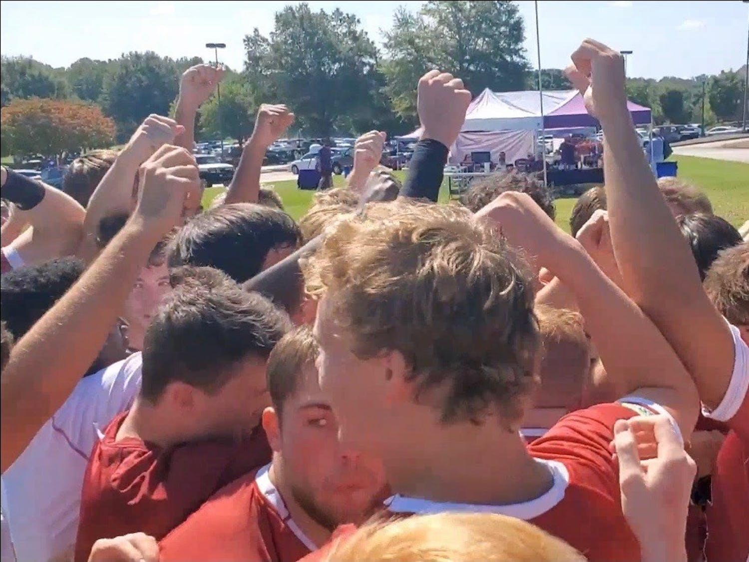Members of the Gamecock club rugby team stand with their fists in the air.