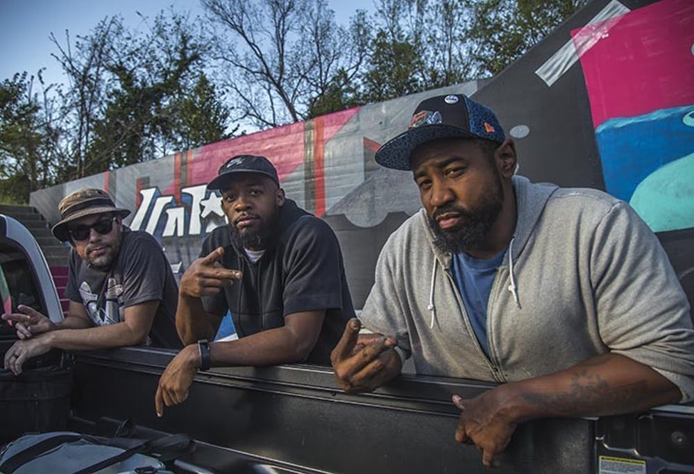 <p>Listed from left to right are Karl Zurfluh, Brandon Donahue and Cedric Umoja, as they work on the triptych mural in Millwood Avenue.</p>