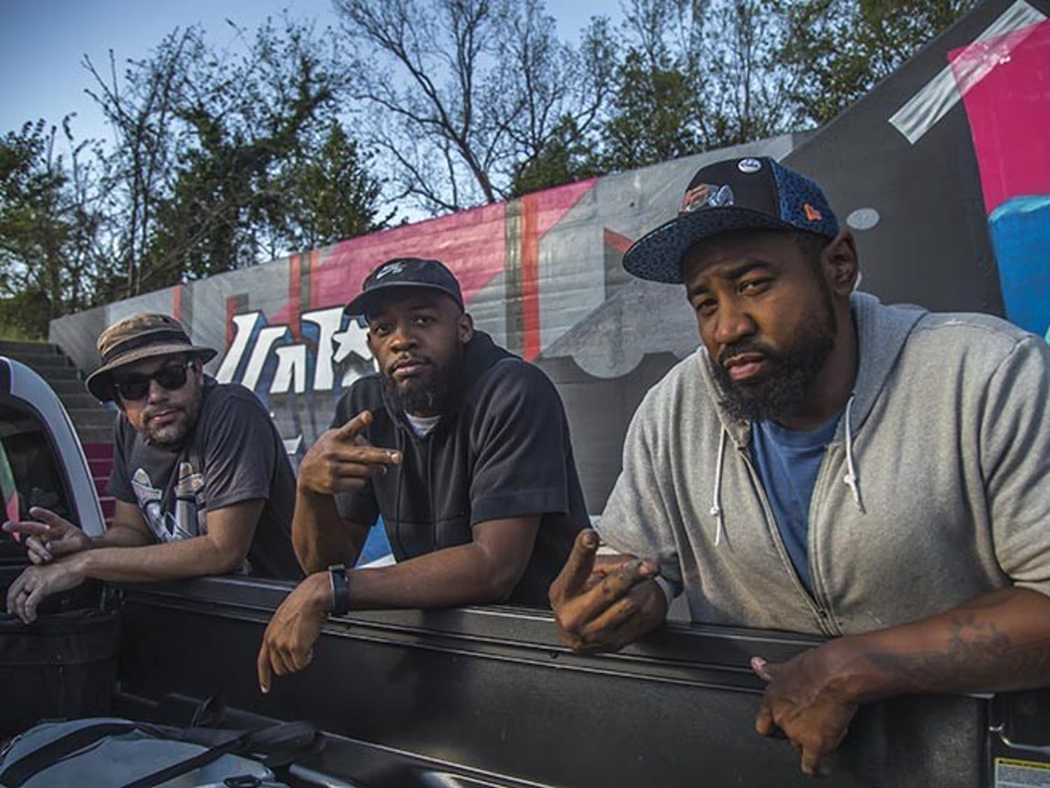 Listed from left to right are Karl Zurfluh, Brandon Donahue and Cedric Umoja, as they work on the triptych mural in Millwood Avenue.