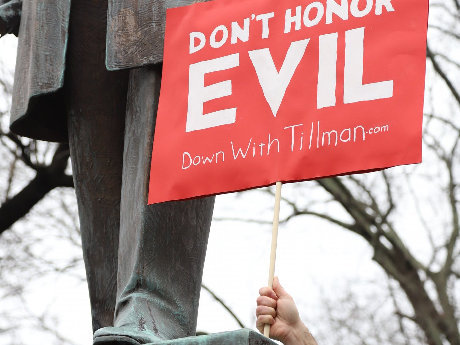 """A protestor holds  a sign that says  """"DON'T HONOR EVIL, Down with Tillman"""" in front of the Benjamin Tillman statue on Tuesday January 12, 2021."""