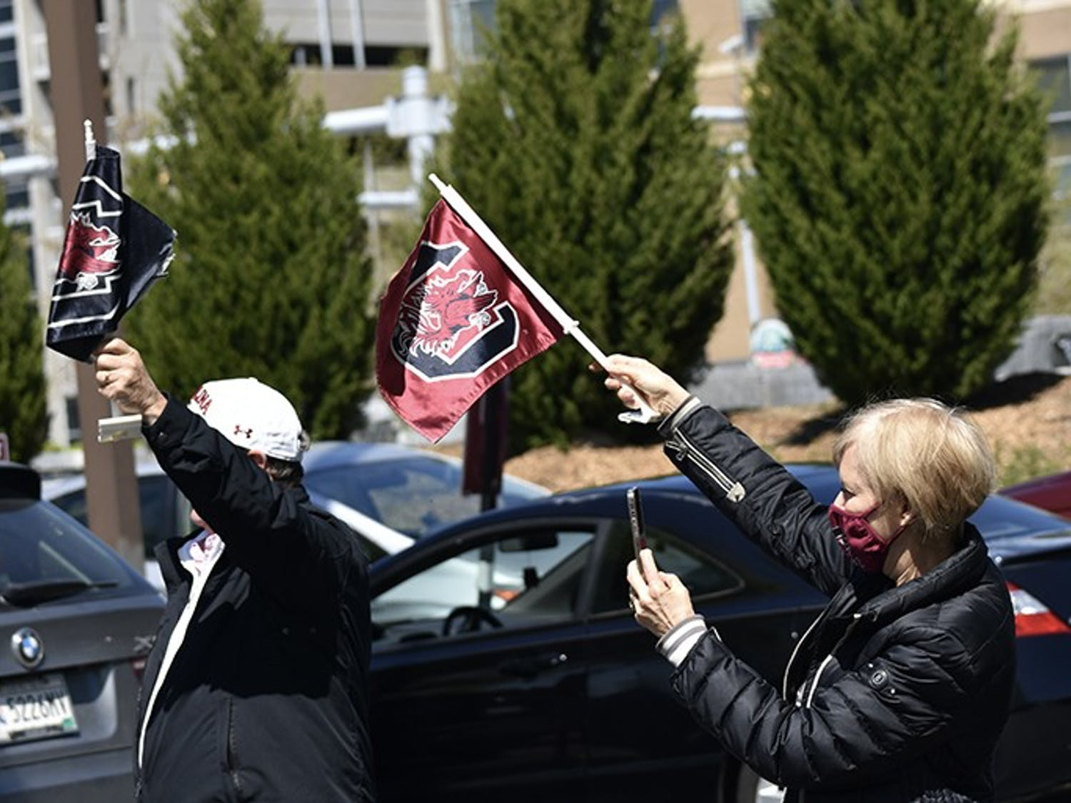 Two fans wave Gamecock flags toward the approaching procession of players.