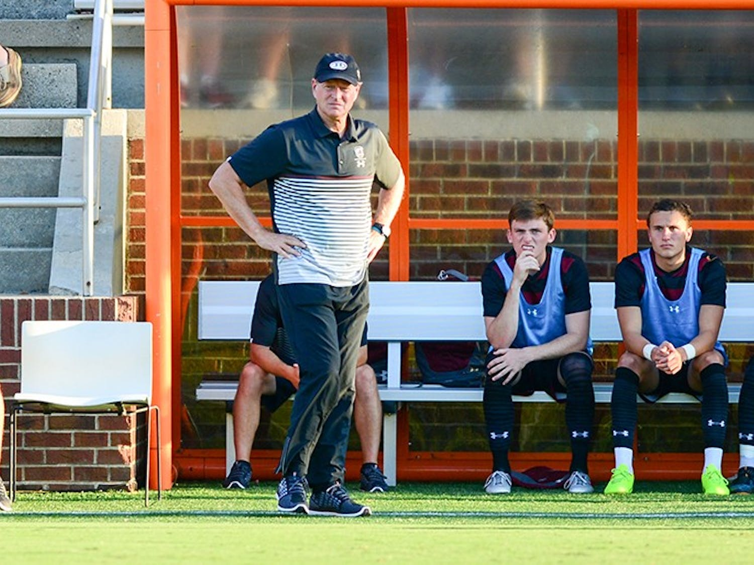 Mark Berson, head coach of South Carolina men's soccer, stands in front of his player sitting on the bench.