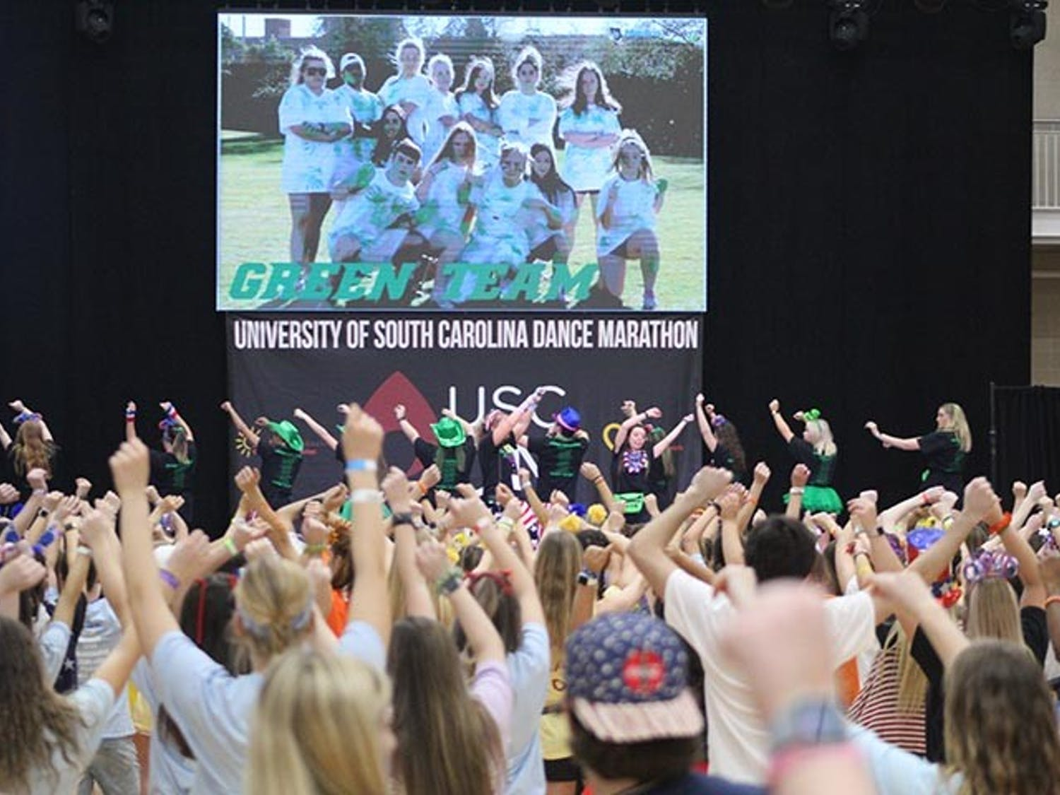 Volunteers and attendees spin around as the Green Team leads them in a line dance at Dance Marathon's Main Event Feb. 29, 2020.