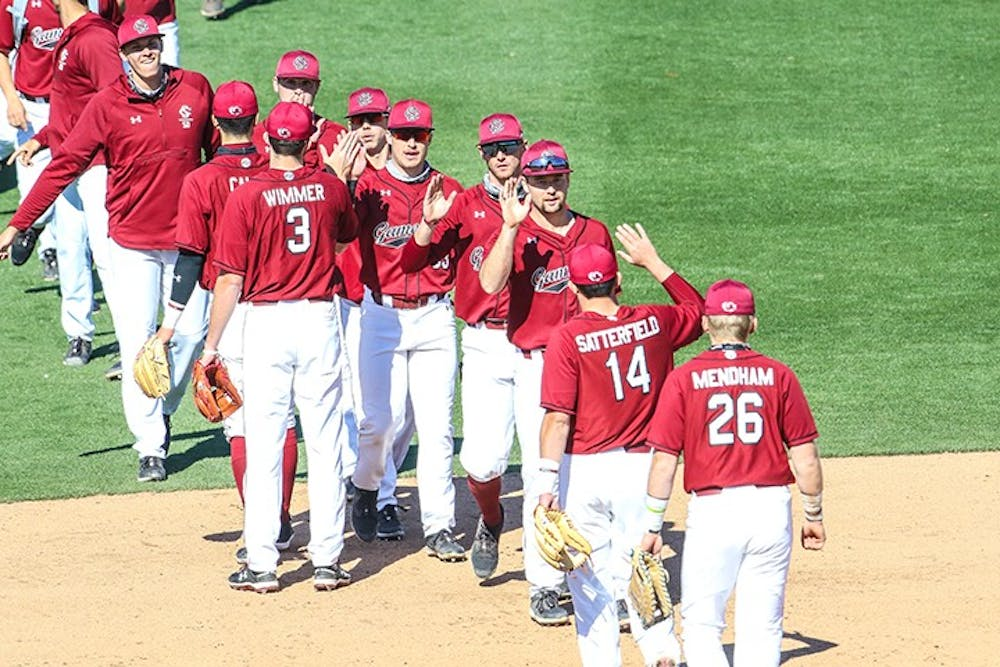 The South Carolina baseball team exchanges high fives after a game.