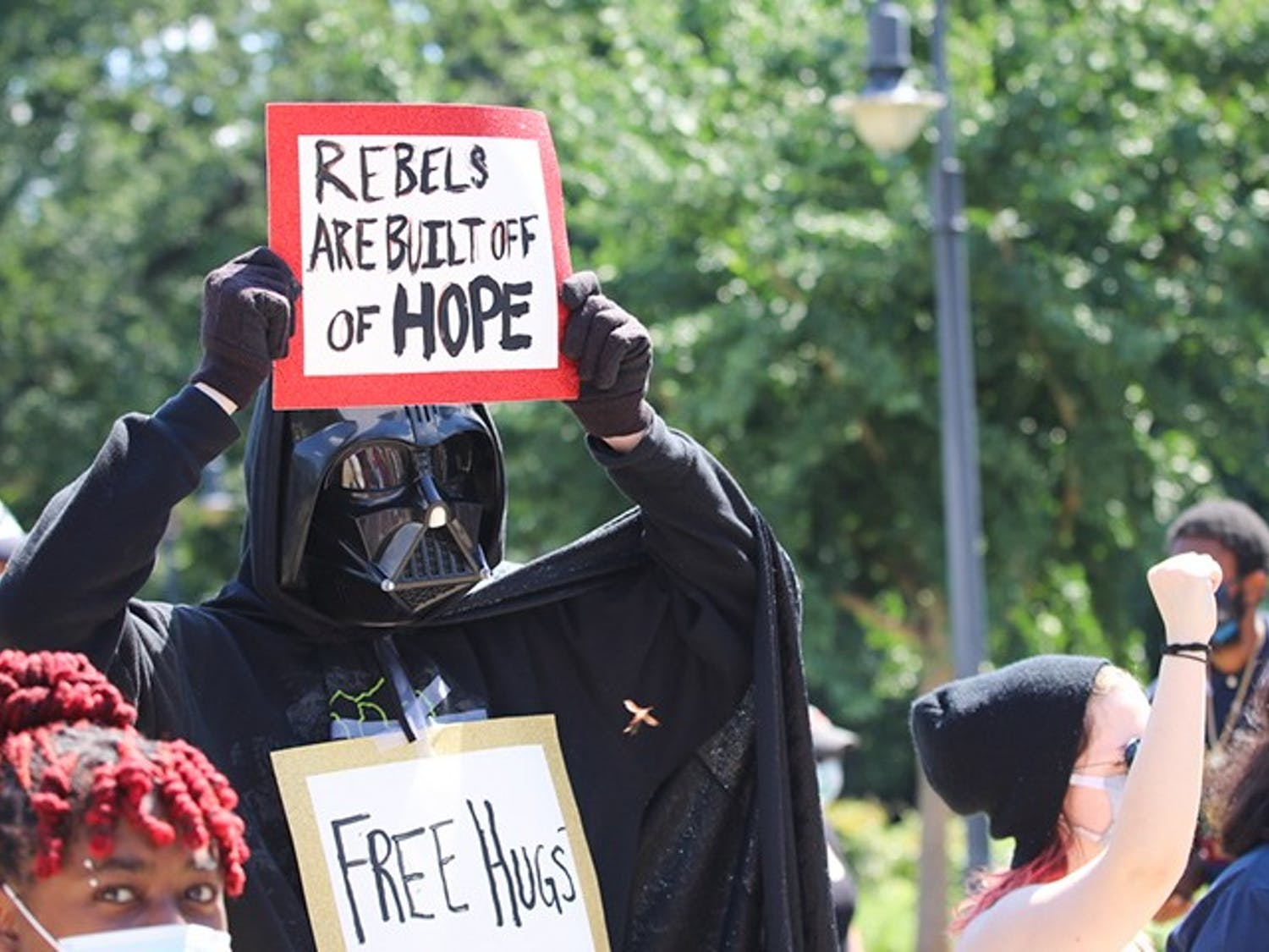 "Dressed in a Darth Vader costume, a protester stood on the side of the street in front of the Statehouse holding a sign that references ""Rogue One: A Star Wars Story."""