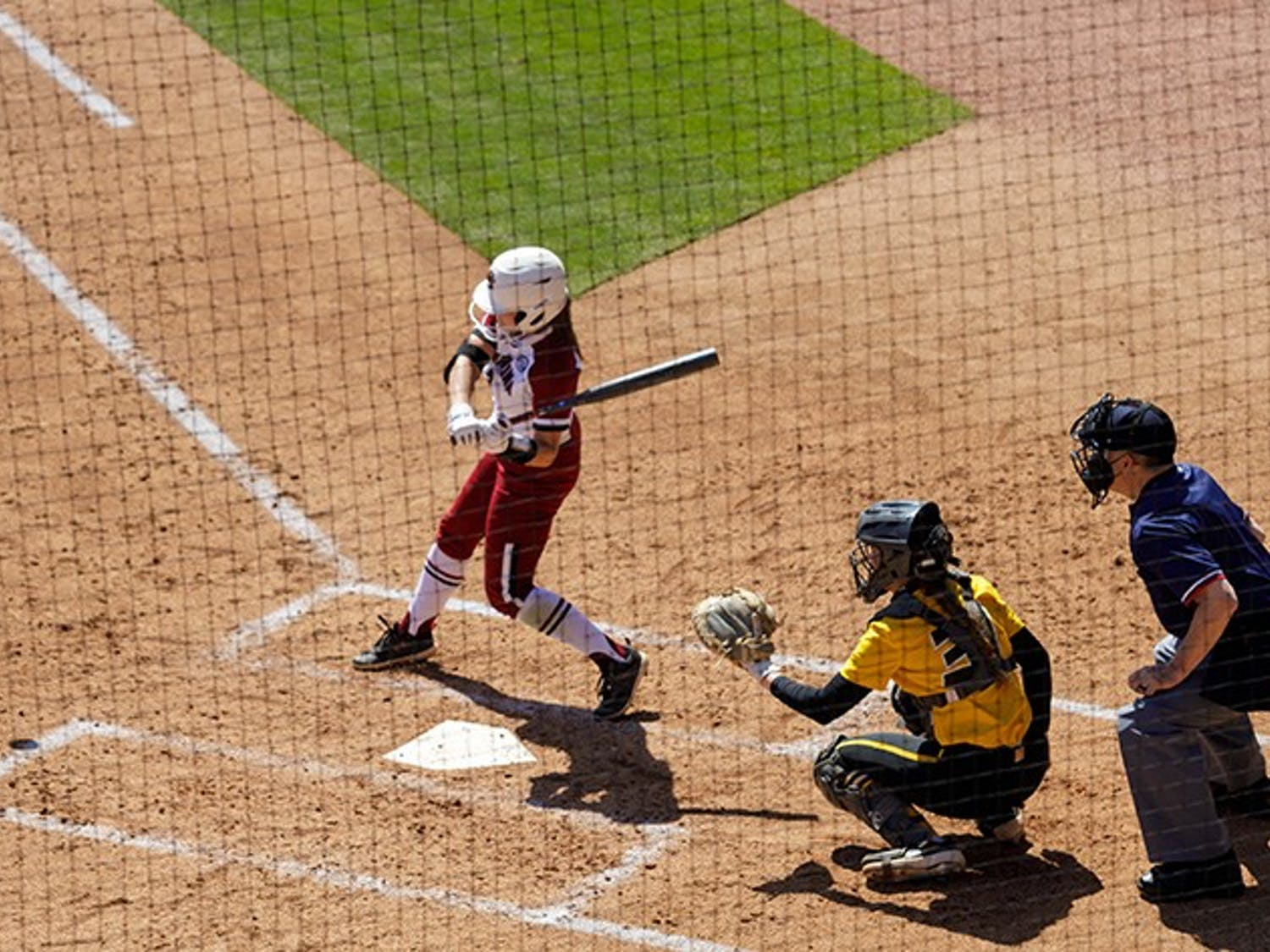 A South Carolina softball player swings the bat at a pitch thrown by the Missouri pitcher.