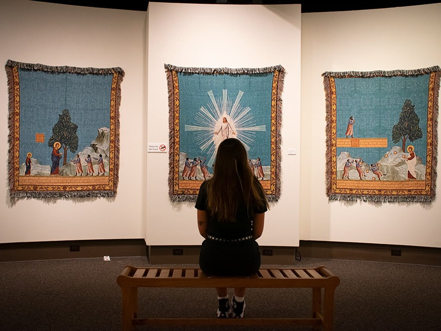 """A museum-goer observes """"Hyphen-ated,"""" an art exhibit in the McKissick Museum. The works of Dan Hernandez and Arturo Rodriguez incorporate ideas of race religion and pop-culture."""