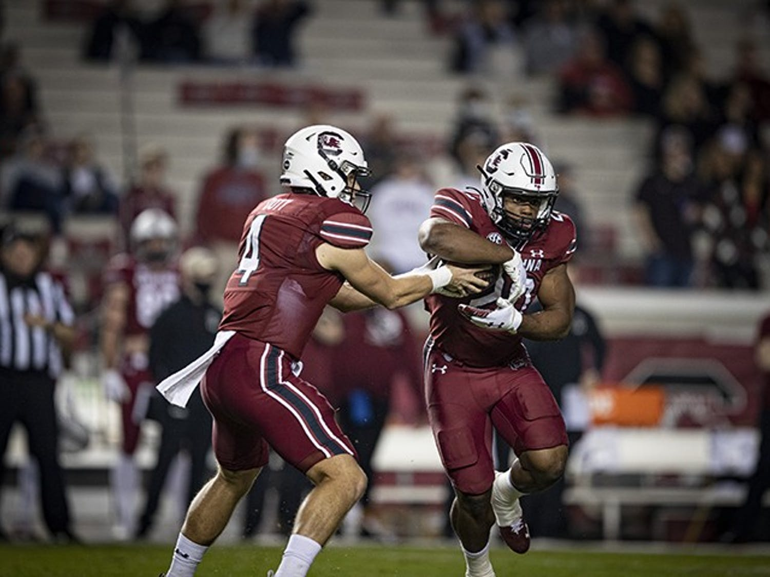 Freshman quarterback Luke Doty hands the ball off to sophomore running back Kevin Harris in South Carolina's loss to Georgia Saturday. The Gamecocks fell to a 2-7 record after the loss.