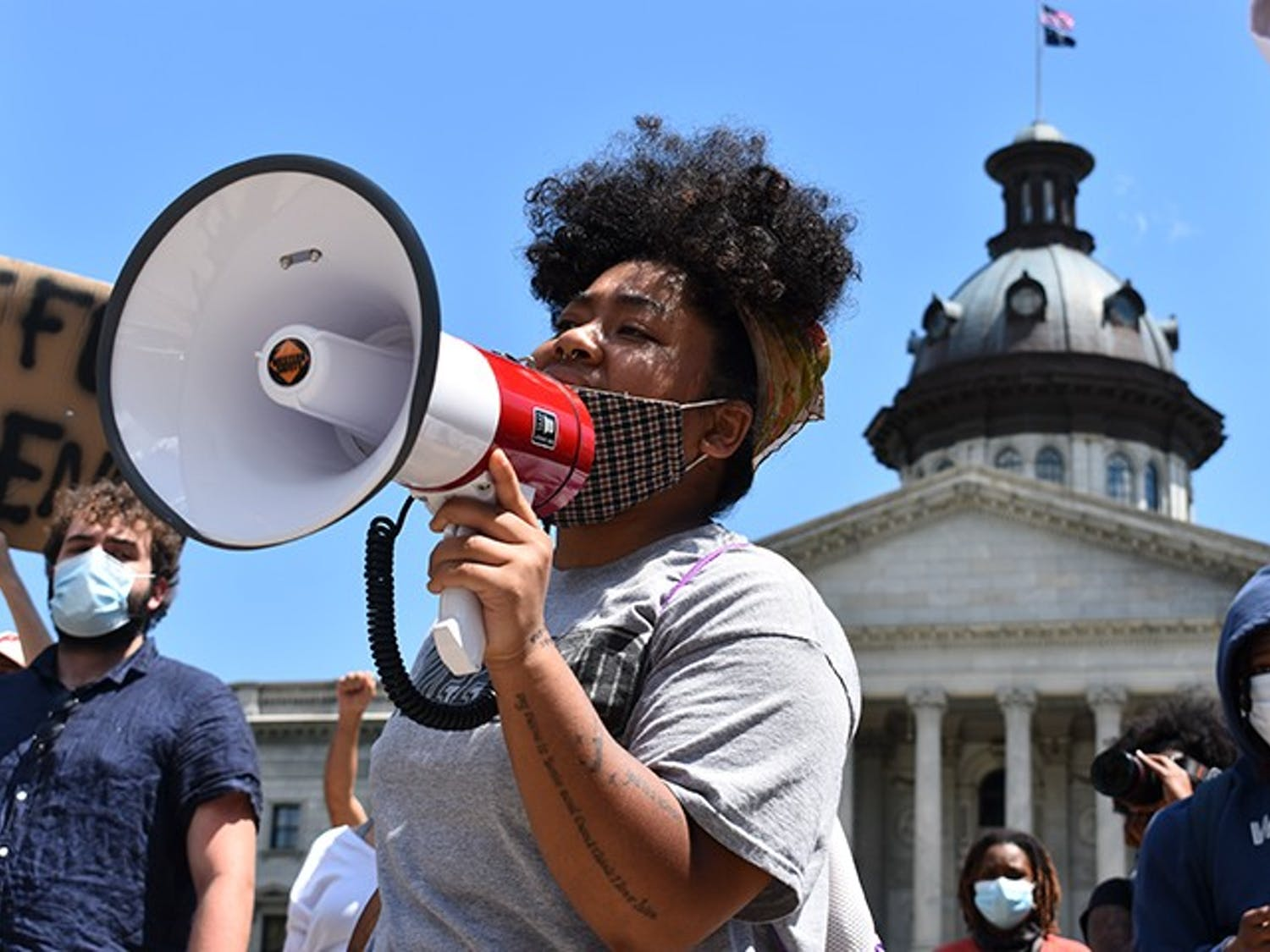 A protester uses a megaphone to lead the crowd in a chant on Monday in front of the Statehouse. The peaceful protesters directed their messages at police officers across the street.