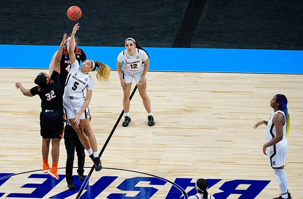 <p>Junior forward Victaria Saxton jumps next to a Mercer player and tries to tip the ball to her fellow teammates. South Carolina beat Mercer in the NCAA Tournament 79-53.&nbsp;</p>
