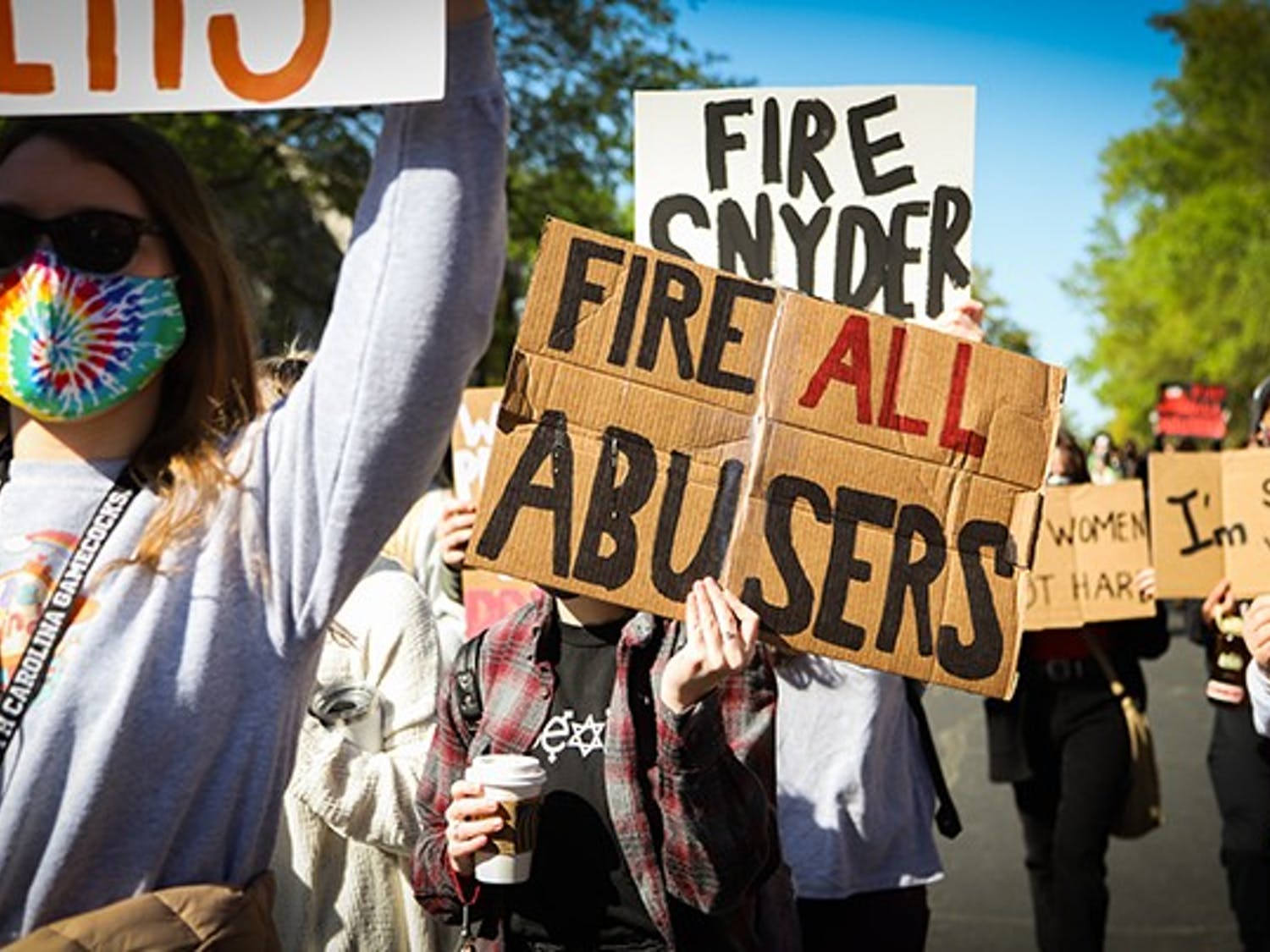 """A marching protestor holds a sign that has the quote, """"FIRE ALL ABUSERS"""" on it, which was written on many signs at the protest."""
