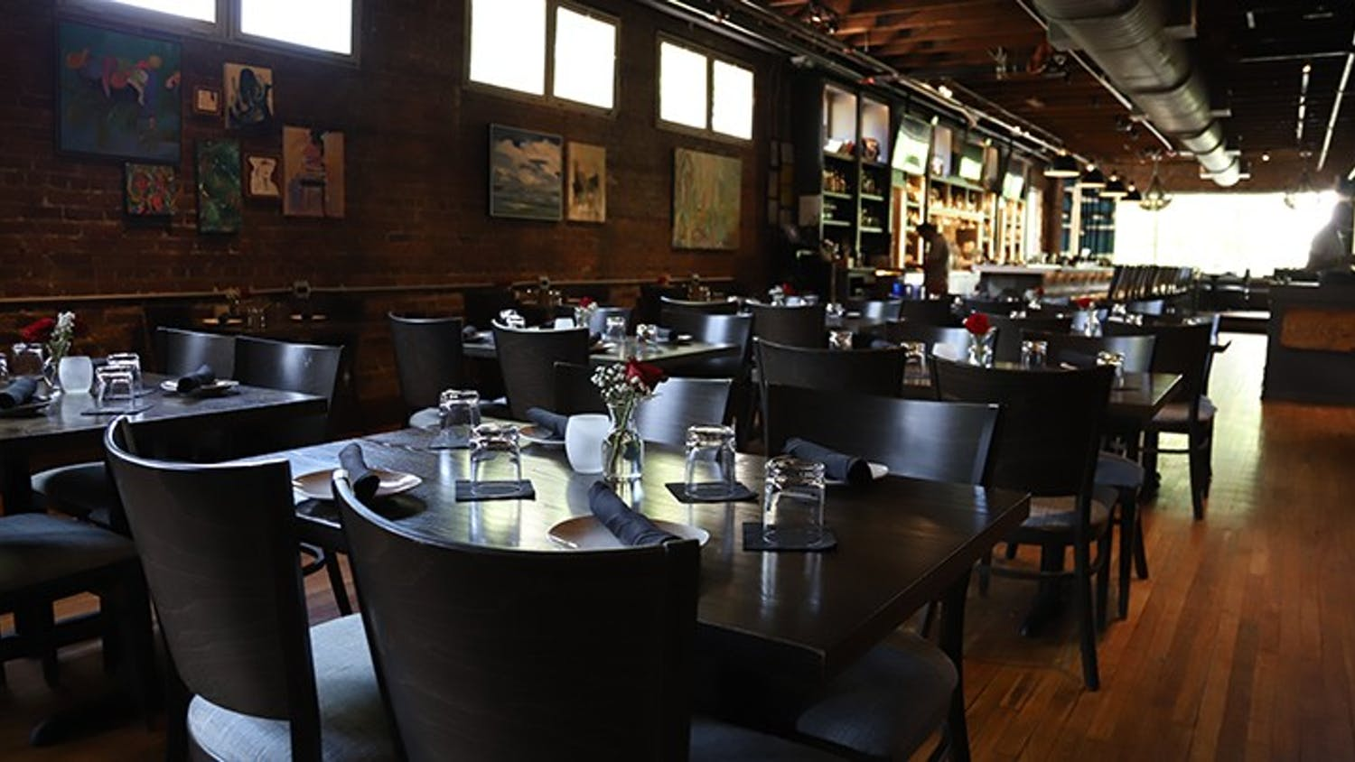 The inside of Hendrix , which is located above The Woody, includes many nicely set tables and a large bar.