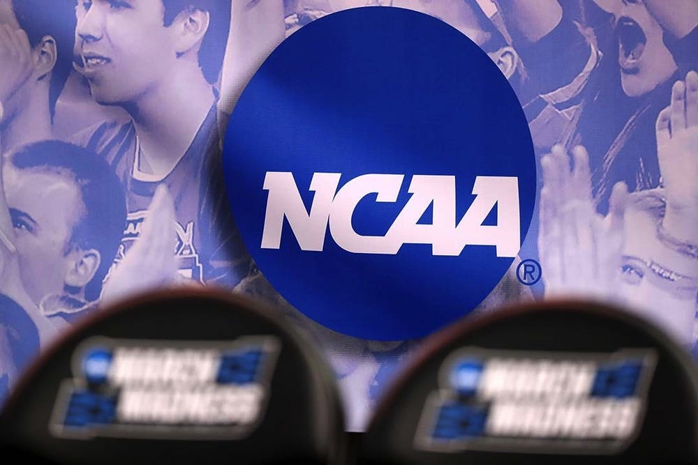 <p>The NCAA logo during the NCAA Men's Basketball Tournament in 2017. The NCAA is changing its rules to allow players within the organization to earn money from their name, image and likeness (NIL).</p>
