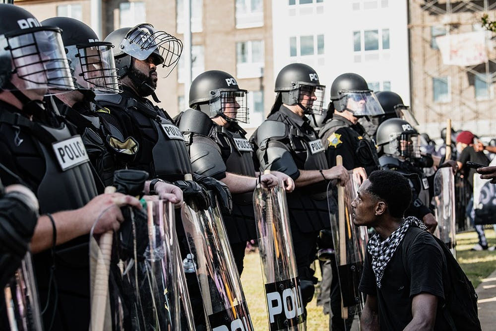 <p>A photograph by Crush Rush, one of the five photo journalists featured at the Hindsight 2020 exhibit, which features pictures of events that defined 2020. This popular image captures a protestor kneeling and looking up at a Black police officer at a police brutality protest at the Statehouse following the death of George Floyd.</p>