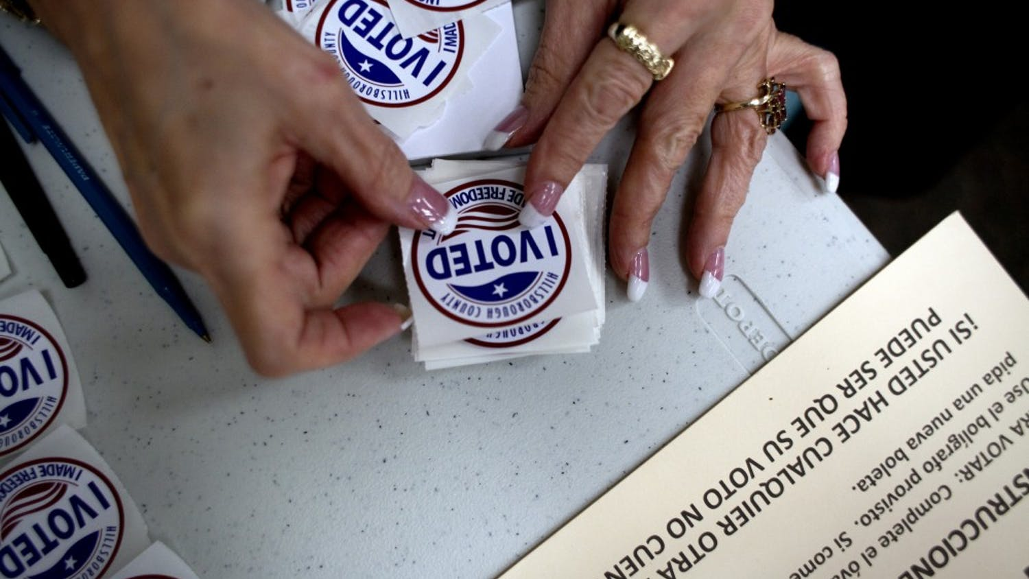 "A poll worker gets ""I Voted"" stickers ready to hand to voters as they finished up at the ballot booths at Jan Kaminis Platt Regional Library in South Tampa, Fla., on November 6, 2012. (Carolina Hidalgo/Tampa Bay Times/TNS)"