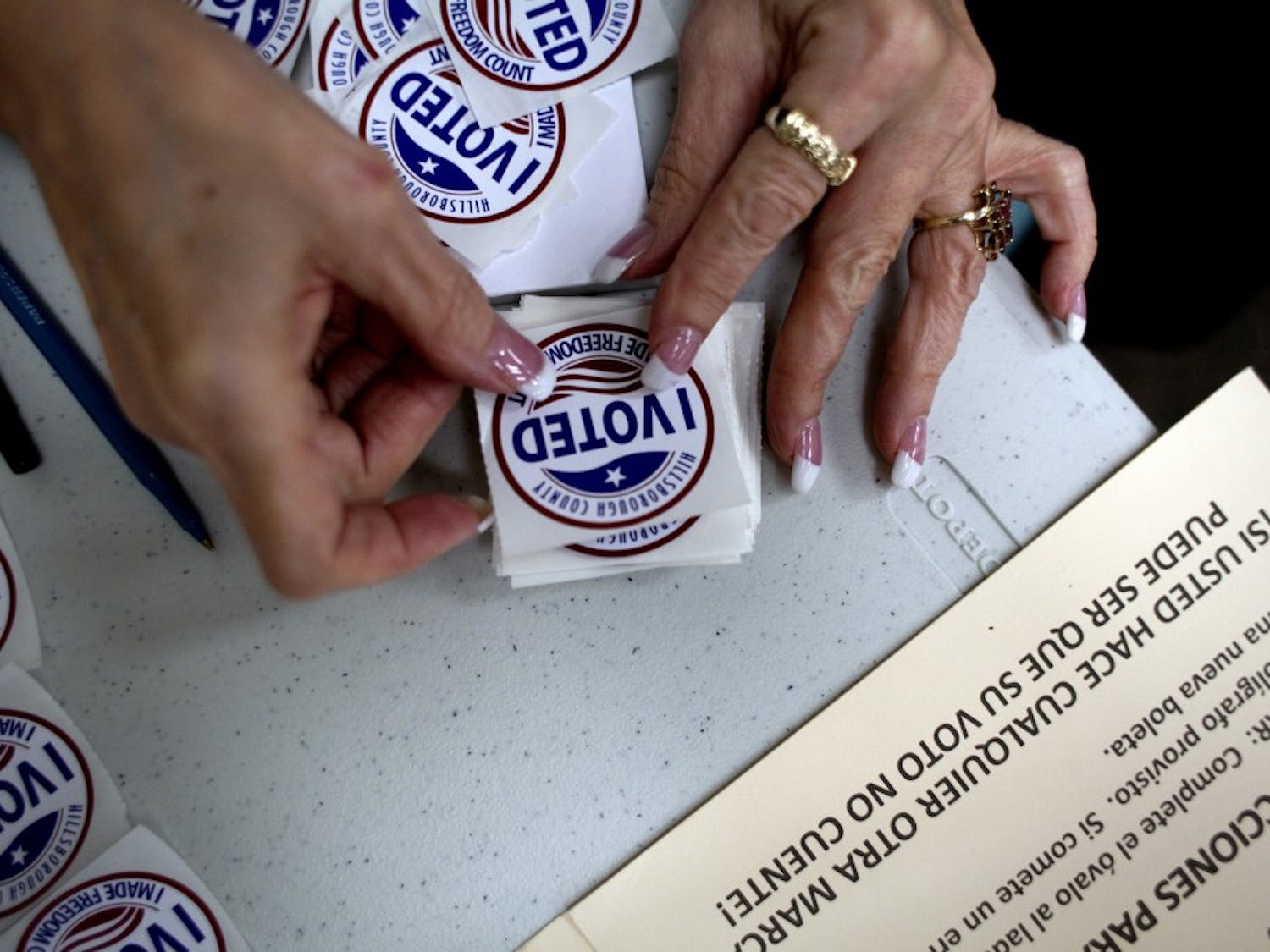 """A poll worker gets """"I Voted"""" stickers ready to hand to voters as they finished up at the ballot booths at Jan Kaminis Platt Regional Library in South Tampa, Fla., on November 6, 2012. (Carolina Hidalgo/Tampa Bay Times/TNS)"""