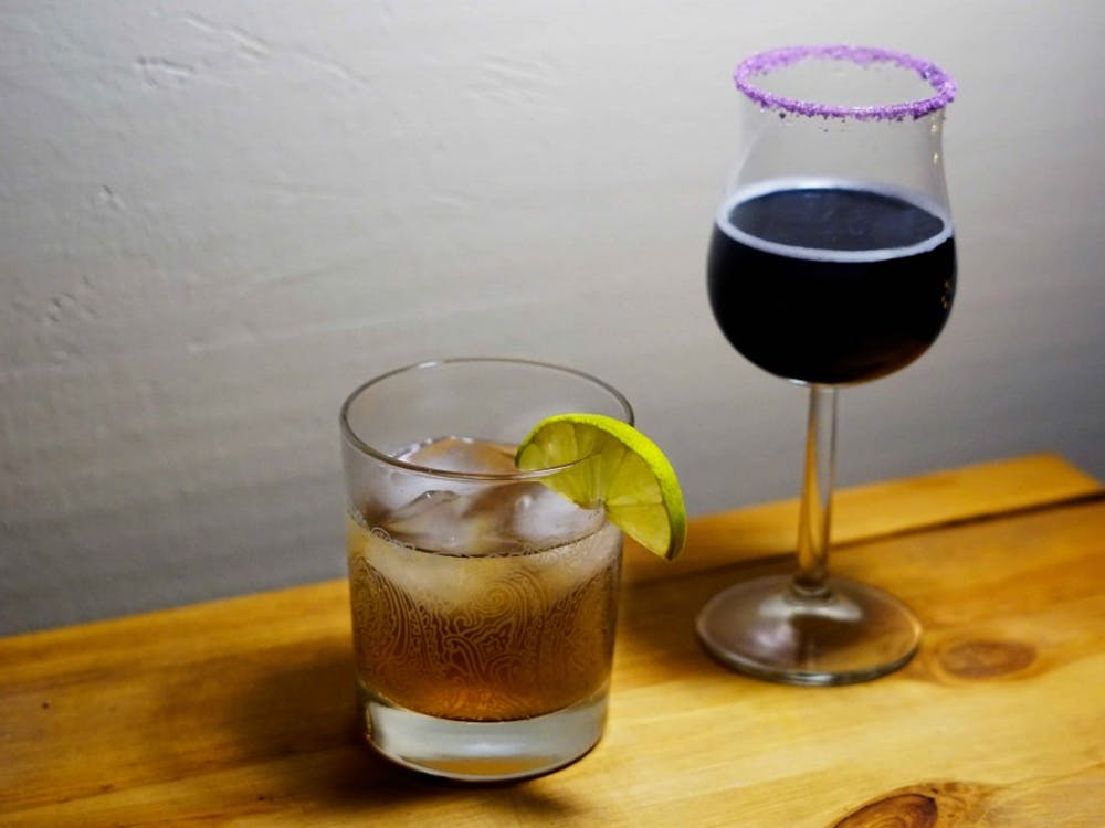 A spicy Dark 'n' Stormy served in a lowball (left) and a festive Purple People Eater in a flared glass rimmed with purple sugar.
