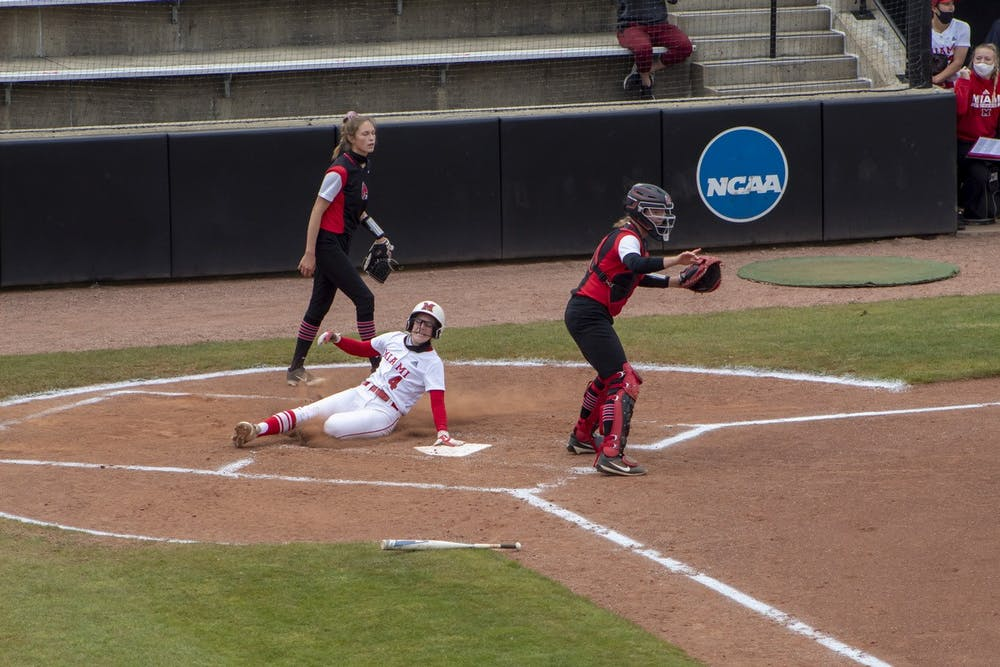 <p>Senior infielder Mackenzie Moore slides into home plate during an April 20 doubleheader vs. Ball State.</p>