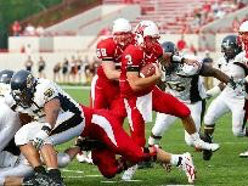 Mike Kokal (3) tucks and runs due to the relentless pressure applied by Kent State. Kokal has been sacked 15 times, tied for the most in Division 1-A.