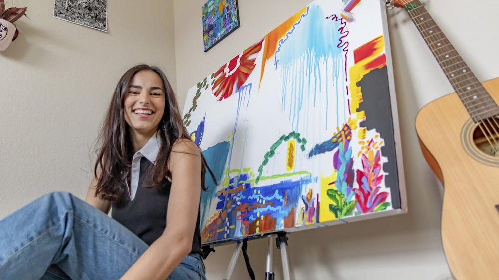 Student artist Sophia Thompson turned to painting for comfort during the pandemic. Behind her is an unfinished piece.