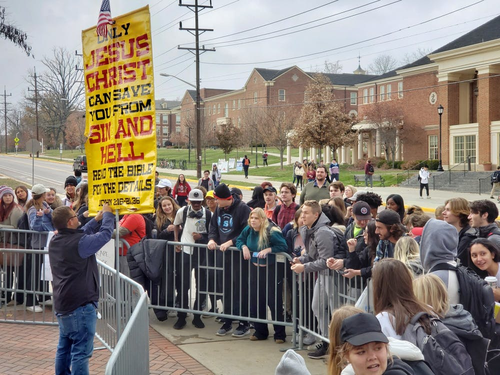 <p>Students shout back and forth with a street preacher at the corner of Spring and Maple. </p>