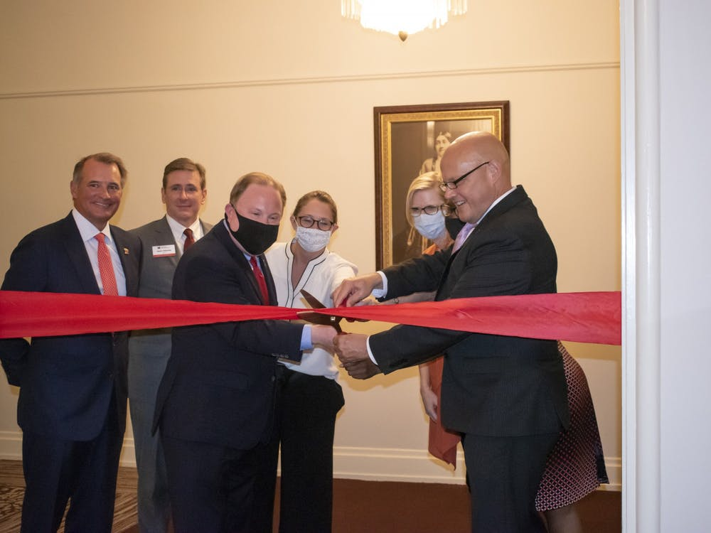 Miami University President Greg Crawford helps cut the ceremonial ribbon inside Peabody Hall on Thursday, Aug. 26, symbolizing the beginning of Miami's new Honors College.