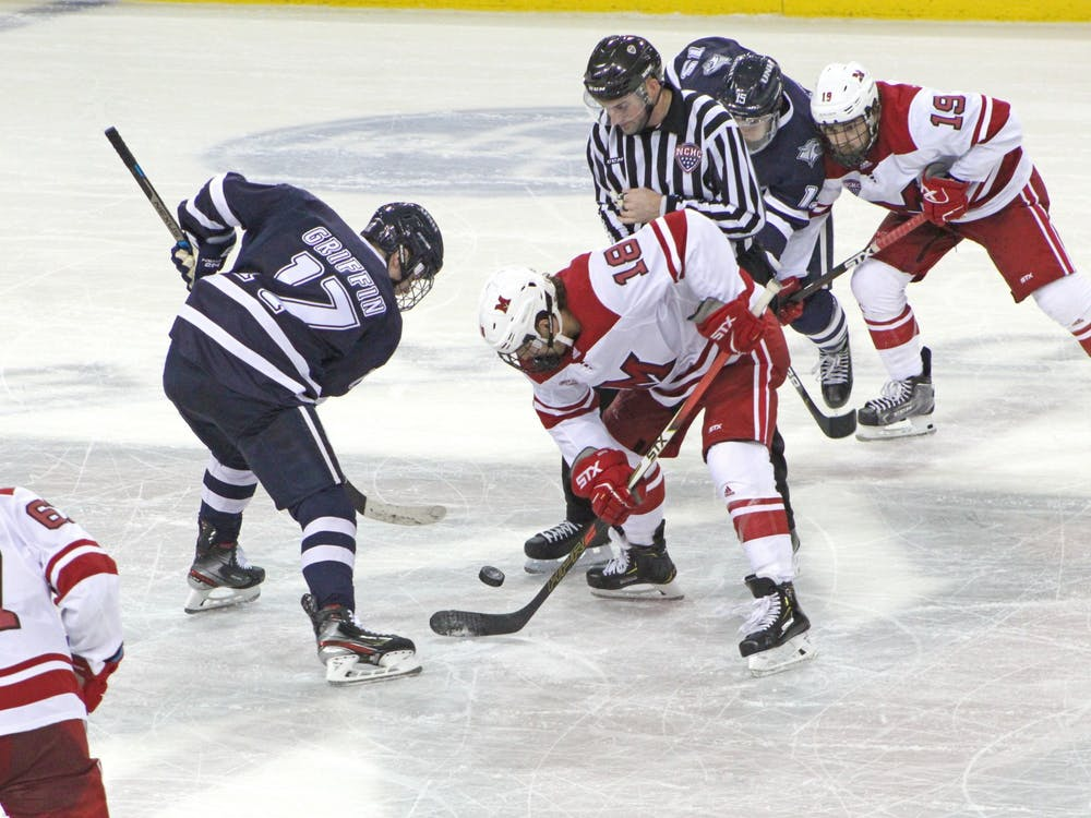 Sophomore forward Monte Graham battles for the puck during a 4-4 tie against New Hampshire on Oct. 12 at the Goggin Ice Center.