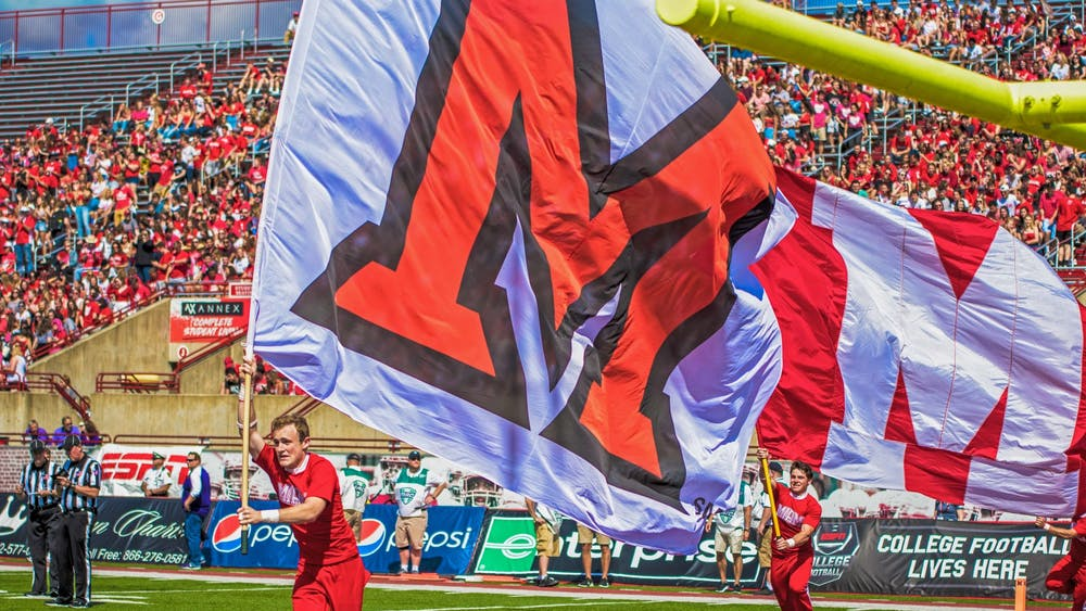 Dane Doebereiner runs across the Yager Stadium end zone with a white Miami flag. The scamper around the field is the Miami cheerleaders customary celebration when the football RedHawks score a touchdown.