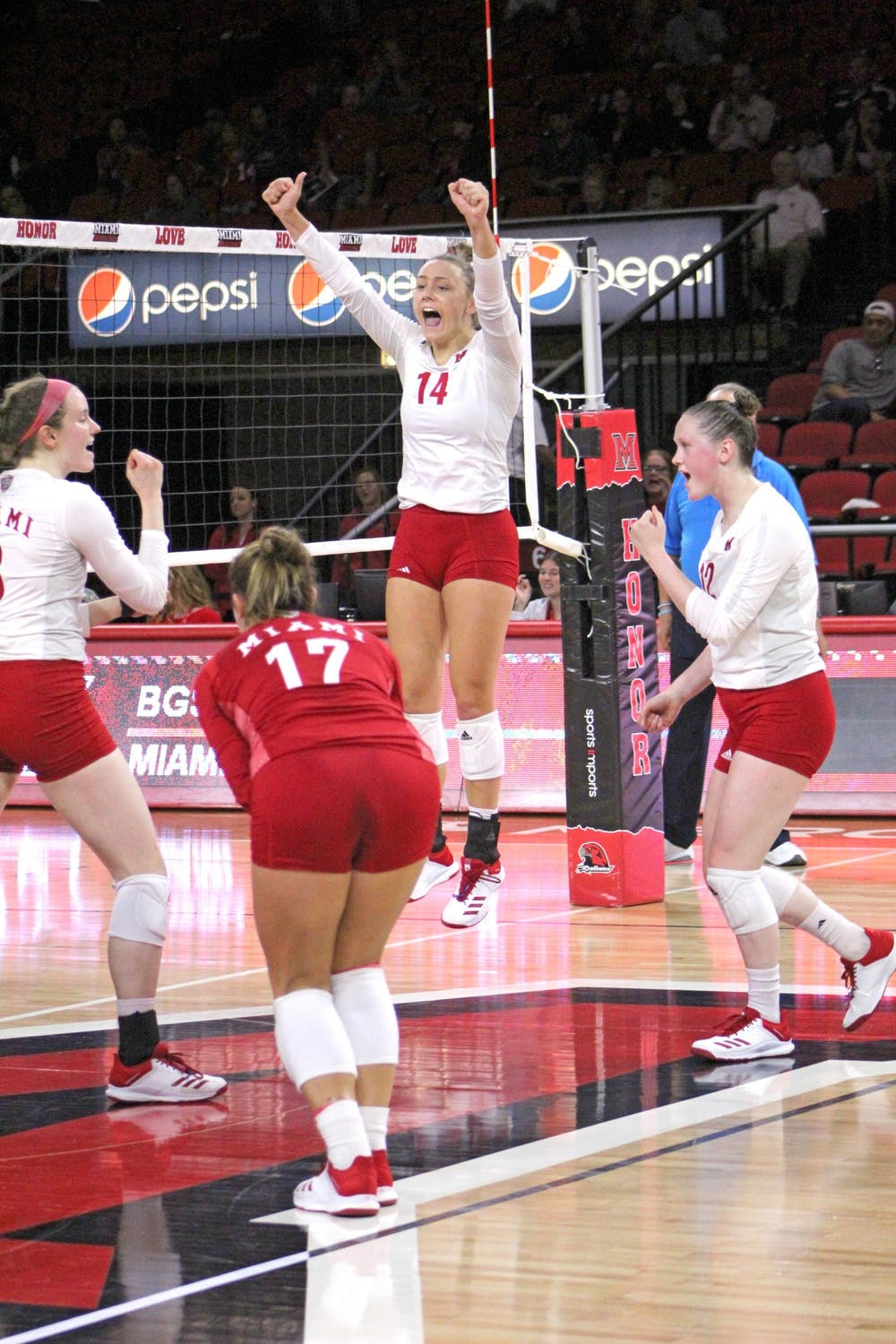 <p>Junior right side Sarah Wojick jumps to celebrate a point with her teammates at Millett Hall. This season, Miami is 8-3 at home.</p>