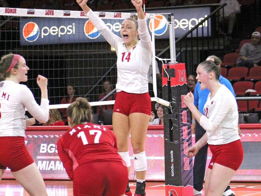 Junior right side Sarah Wojick jumps to celebrate a point with her teammates at Millett Hall. This season, Miami is 8-3 at home.